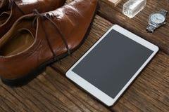 Ботинки, цифровая таблетка и наручные часы на деревянной планке Стоковые Изображения RF