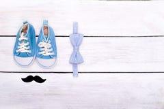 Ботинки ` s детей, ложь бабочки на белой деревянной предпосылке Взгляд Стоковое Изображение RF