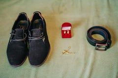 Ботинки ` s людей, кожаный пояс для брюк, обручальные кольца в красной коробке и держатель связи, атрибуты ` s groom стоковое изображение