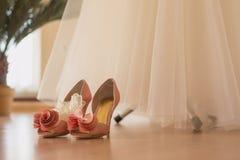 Ботинки ` s невесты стоят на поле около платья свадьбы Стоковая Фотография