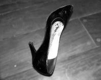 Ботинок женщины лежа на поле Пятка женщины высокая Черные шпильки лежа на поле Изолированный ботинок женщины Черно-белый ботинок Стоковая Фотография RF