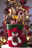 Ботинок Санта Клауса вполне с ханжами рождества закрывает вверх по рождественской елке в предпосылке Стоковые Фотографии RF