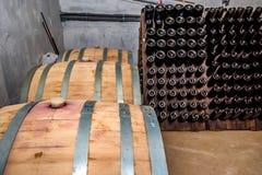 Бочки и бутылки вина в погребе Стоковая Фотография