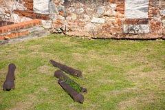 4 бочонка старого карамболя на зеленой траве около стены старой крепости Стоковое Фото
