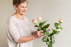 Более старая женщина аранжируя розы стоковые изображения rf