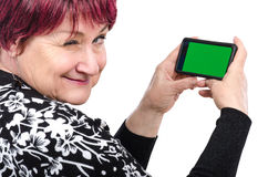 Более старая женщина держа мобильный телефон подмигивает на камере стоковые изображения