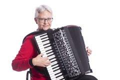 Более старая женщина играет аккордеон в студии против белой предпосылки стоковое изображение