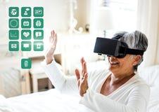 Более старая женщина нося шлемофон виртуальной реальности VR с интерфейсом здоровья медицинским стоковое изображение
