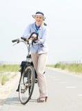 Более старая женщина ослабляя с велосипедом на пути сельской местности Стоковое Фото