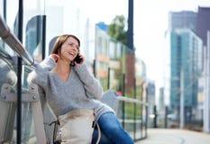 Более старая женщина сидя снаружи в городе говоря на мобильном телефоне Стоковые Изображения RF