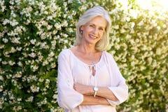 Более старая женщина усмехаясь и стоя снаружи весной стоковое изображение