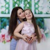 Более старая и более молодая сестра обнимая знак сердца выставки руками Стоковые Изображения RF