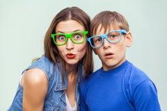 Более старая сестра и ее брат при веснушки, представляя над светом - голубой предпосылкой совместно на временени, смотря камеру Стоковая Фотография RF