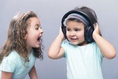 Более старая сестра кричащая на ее более молодой сестре в наушниках Стоковое Изображение RF
