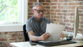 Более старый бизнесмен работая на столе в студии дизайна сток-видео
