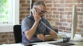 Более старый бизнесмен сидя на столе на телефоне в студии дизайна акции видеоматериалы