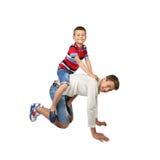 Более старый мальчик носит заднюю часть маленького брата дальше изолированную на белом backg стоковое изображение