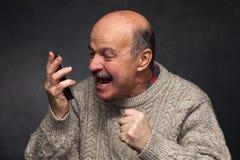 Более старый человек выкрикивает в телефон в гневе Стоковая Фотография