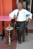 Более старый человек курит кальян Стоковая Фотография RF