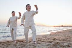 2 более старых люд практикуя Taijiquan на пляже на заходе солнца, Китае Стоковые Фотографии RF
