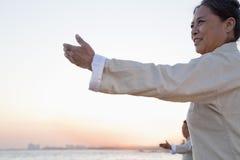 2 более старых люд практикуя Taijiquan на пляже на заходе солнца, Китае Стоковые Фото