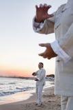 2 более старых люд практикуя Taijiquan на пляже на заходе солнца, конце вверх на руках Стоковые Изображения RF