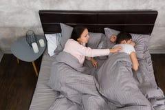 Бодрствование молодой женщины вверх по ее обиденному парню пока лежащ в быть Стоковые Фото