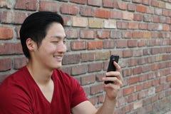 Болтовня телефона Выстрел в голову портрета крупного плана азиатского человека отправляя СМС на мобильном телефоне на предпосылке стоковые изображения rf