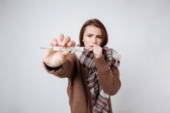 Больная женщина в свитере и шарфе показывая термометр Стоковые Фотографии RF