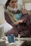 Больная женщина в спальне с пилюльками гриппа Стоковая Фотография RF