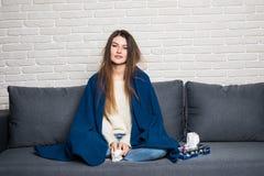 Больная женщина лежа на софе дома стоковая фотография
