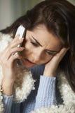 Больная женщина зноня по телефону в больном для работы на мобильном телефоне стоковое фото rf