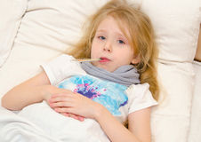 Больная маленькая девочка лежа в кровати с температурой стоковое изображение