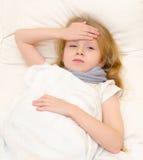 Больная маленькая девочка лежа в кровати Стоковые Фотографии RF