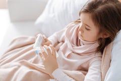 Больная маленькая девочка принимая пилюльки Стоковые Фото