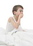 Больной кашлей мальчика в белой кровати стоковое изображение