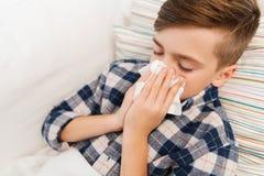 Больной мальчик лежа в кровати и дуя его нос дома Стоковое Изображение