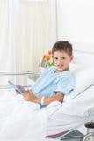 Больной мальчик держа цифровую таблетку в больнице стоковая фотография