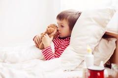 Больной мальчик ребенка лежа в кровати при лихорадка, отдыхая стоковые фото