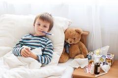 Больной мальчик ребенка лежа в кровати при лихорадка, отдыхая стоковые фотографии rf