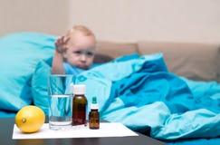 Больной младенец лежа в кровати и смотря термометр Стоковое фото RF