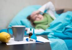 Больной младенец лежа в кровати перед ее стороной дает наркотики Стоковые Изображения RF