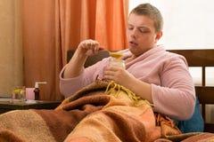 Больной парень в розовом купальном халате лежа в кровати и есть мед стоковые изображения rf