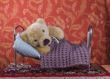 Больной плюшевый медвежонок в кровати с термометром Стоковые Изображения