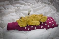 Больной плюшевый медвежонок лежа с горячеводной бутылкой и термометром Стоковое фото RF