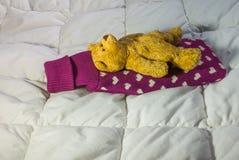 Больной плюшевый медвежонок лежа с горячеводной бутылкой на его назад Стоковая Фотография RF