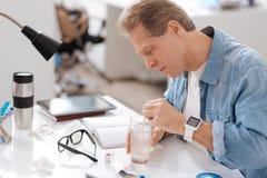 Больной работник офиса шевеля его медицину Стоковая Фотография RF