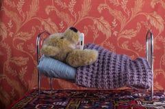 Больной сиротливый плюшевый медвежонок лежа с термометром в кровати Стоковые Изображения