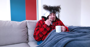 Больной человек держит чашку пока сидящ на кресле стоковые изображения rf
