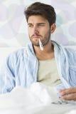Больной человек с термометром в рте сидя на кровати стоковое изображение rf
